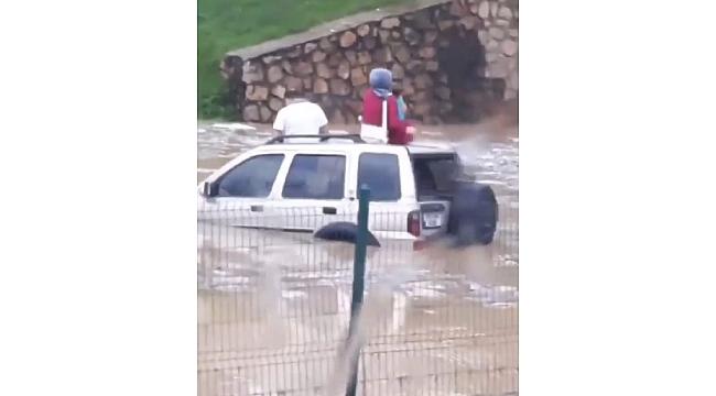 Su altında kalan aracın tavanına çıktılar!